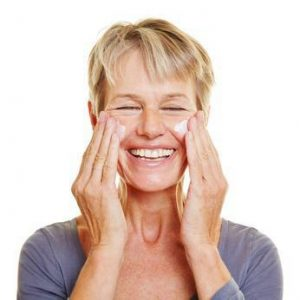 Ältere Frau pflegt Haut mit Creme